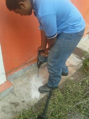 Mengorek lubang untuk menyuntik racun anti anai-anai ke dalam tanah
